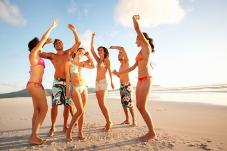 Group of teenagers dancing on the sea shore